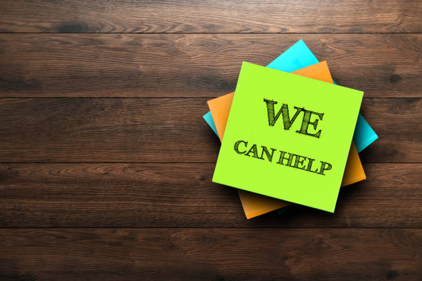nós podemos ajudar, a frase é escrita em etiquetas coloridas, sobre um fundo de madeira marrom. conceito de negócio, estratégia, plano, planejamento. - apoio - fotografias e filmes do acervo