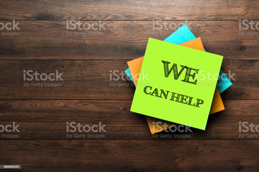 We Can Help, the phrase is written on multi-colored stickers, on a brown wooden background. Business concept, strategy, plan, planning. stock photo