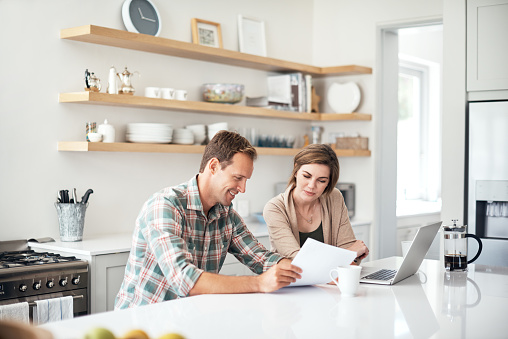 Shot of a couple using a laptop while going through paperwork together at home
