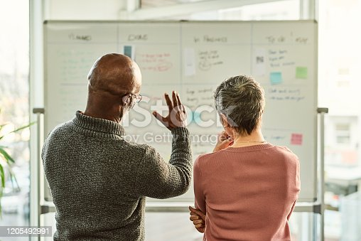 Cropped shot of two unrecognizable businesspeople standing together and using a white board during a discussion in the office
