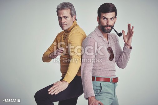 Studio shot of two men standing together while wearing retro 70s wear and striking a fighting pose