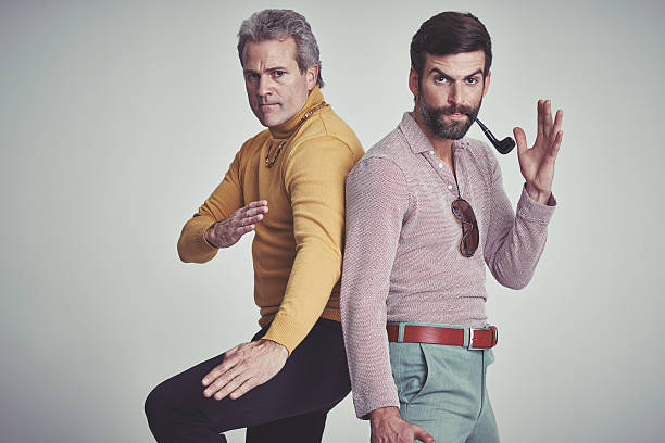 We can totally take you! Studio shot of two men standing together while wearing retro 70s wear and striking a fighting pose confrontation stock pictures, royalty-free photos & images