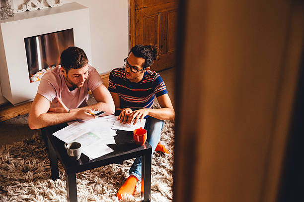 We Can't Afford It Male couple looking through financial documents together in their home. One of them is using his smartphone as a calculator which they are both looking at dissapointedly. mortgages and loans stock pictures, royalty-free photos & images