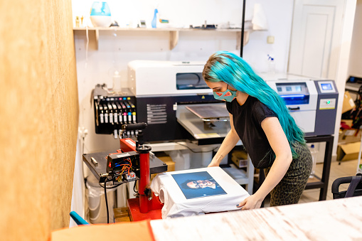 Young female business owner , with dyed blue hair printing t-shirt in the silk screen printing machine at her workshop while wearing protective face mask during COVID-19