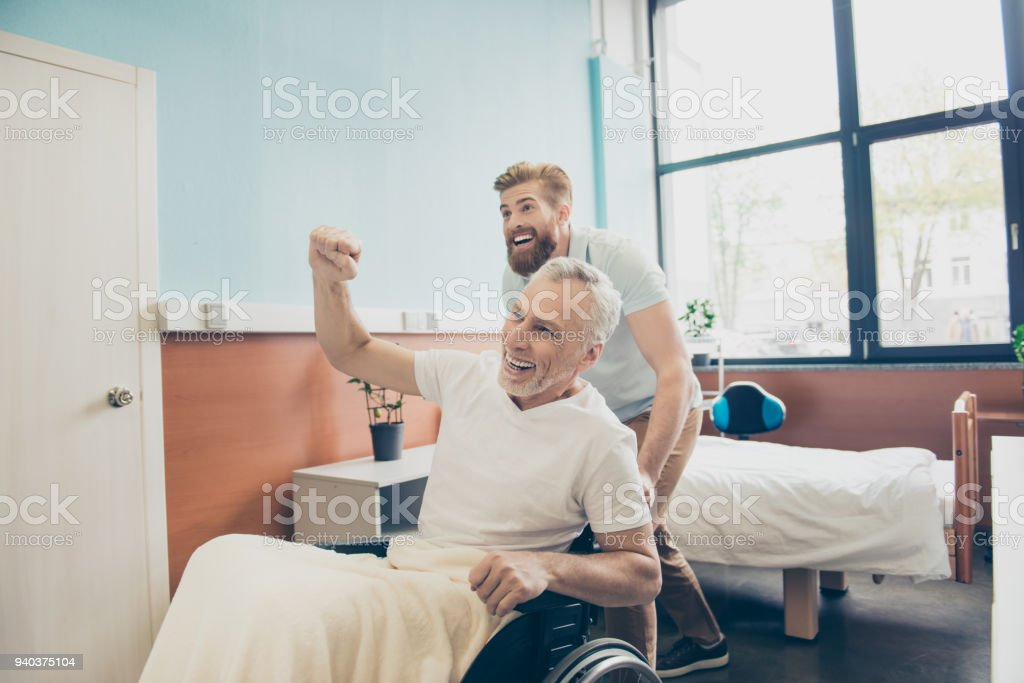 We did it! Cheerful family is celebrating good end of hard surgery that old patient had, they are leaving ward together stock photo