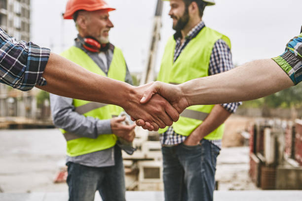 We did it! Close up photo of builders shaking hands against cheerful colleagues while working together at construction site. Team work. We did it! Close up photo of builders shaking hands against cheerful colleagues while working together at construction site. Team work. Construction concept. Building concept diad stock pictures, royalty-free photos & images