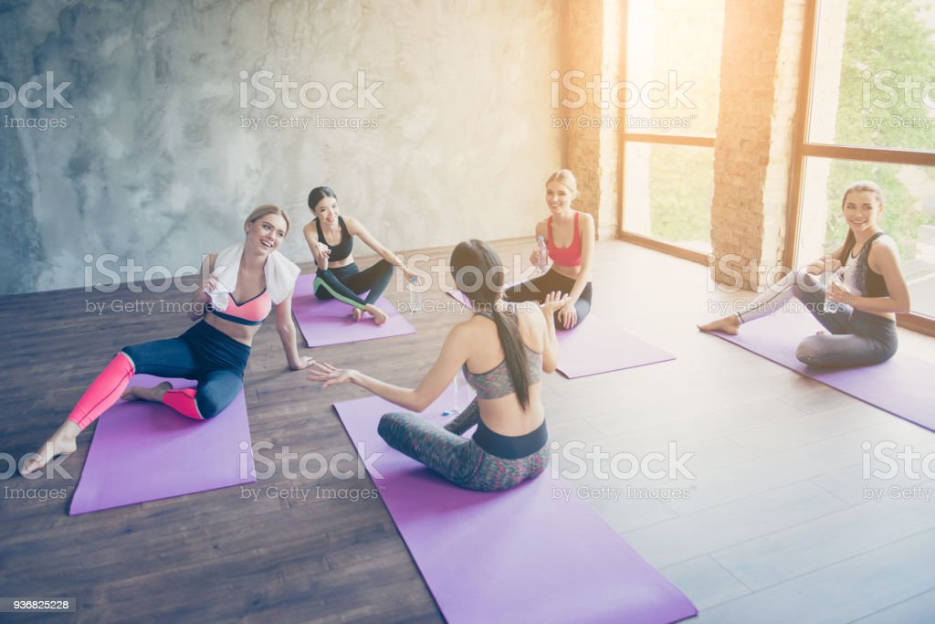 We did it! Five cheerful girls are resting after work out, drinking...