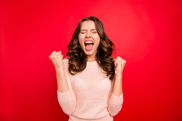 we did it! portrait of closed eyes raised fists up woman in casual wear isolated on vivid red background with closed eyes and wide open mouth. - smile woman open mouth foto e immagini stock