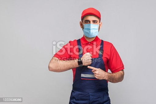 1047558948 istock photo We do ontime. Young man with surgical medical mask in blue overall and red t-shirt standing and showing time on his wrist watch with smile. 1222538086