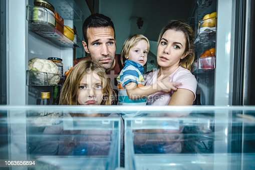 Sad family looking in an empty refrigerator.