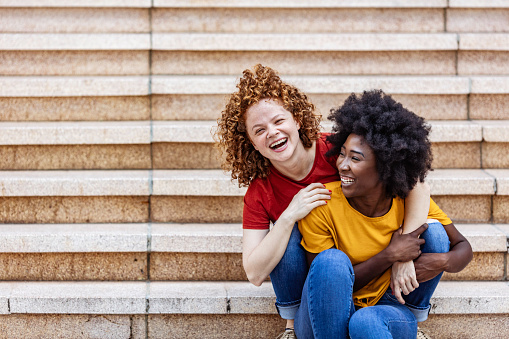 Two happy multi ethnic female friends Couple Hugging Each Other while sitting on steps outdoors .Two diverse Lesbian Women Outdoors. LGBT Concept.