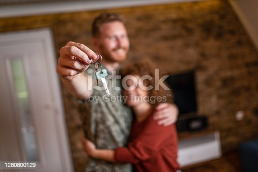 Happy young ginger couple just moved in their new apartment. Holding home keys in front of camera.