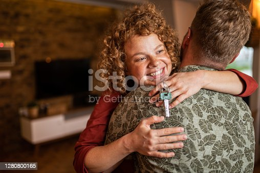 Happy young woman hugging her boyfriend in their new apartment and holding home keys.