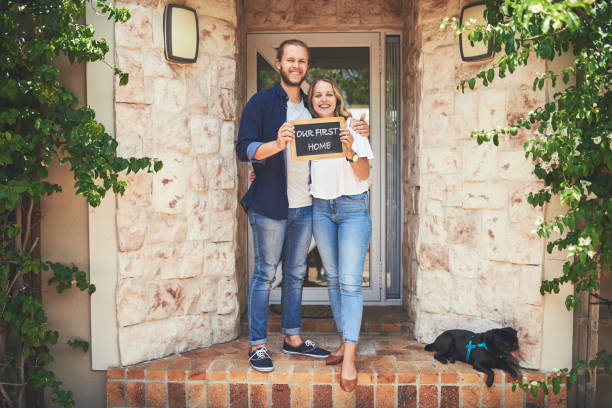 """We found a place to call ours Portrait of a young couple holding a chalkboard with """"our first home"""" written on it home ownership stock pictures, royalty-free photos & images"""