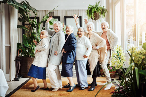 We found the fountain of youth…it's called having fun! Portrait of a group of happy senior women having fun together at a retirement home aging stock pictures, royalty-free photos & images