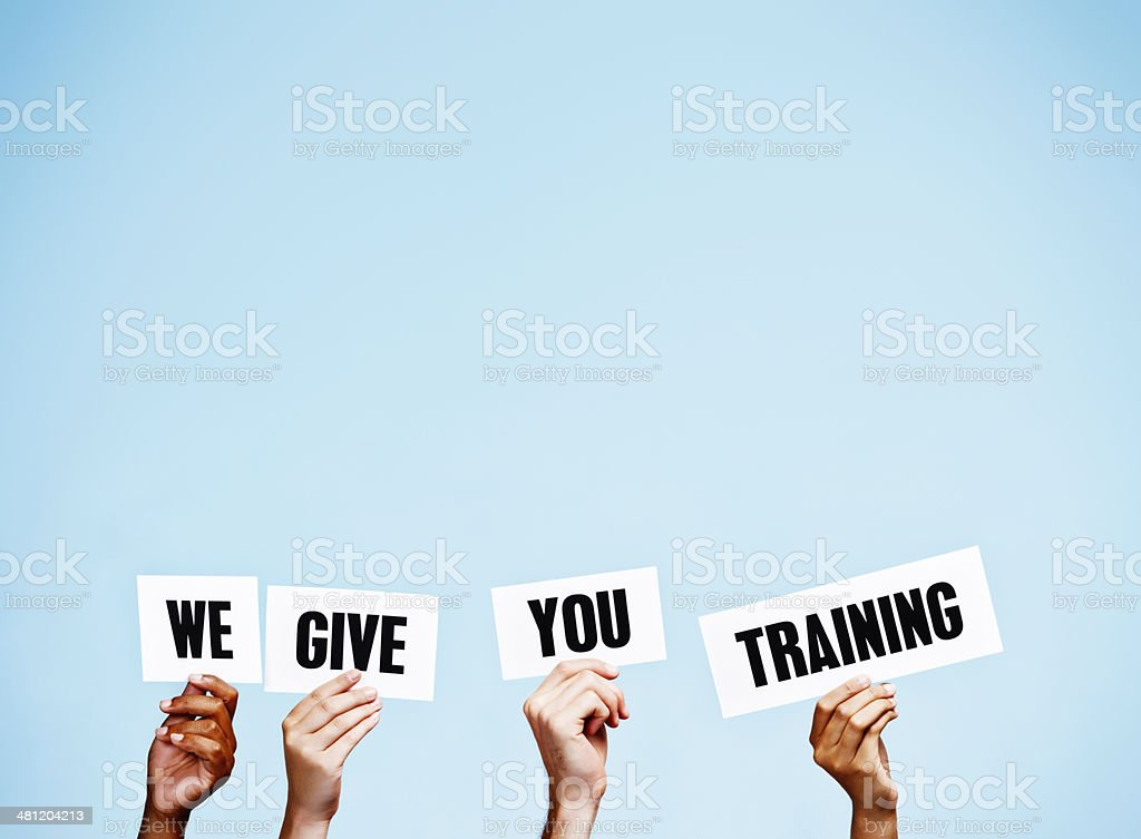 'We give you Training' say hand-held signs: It's vital! stock photo