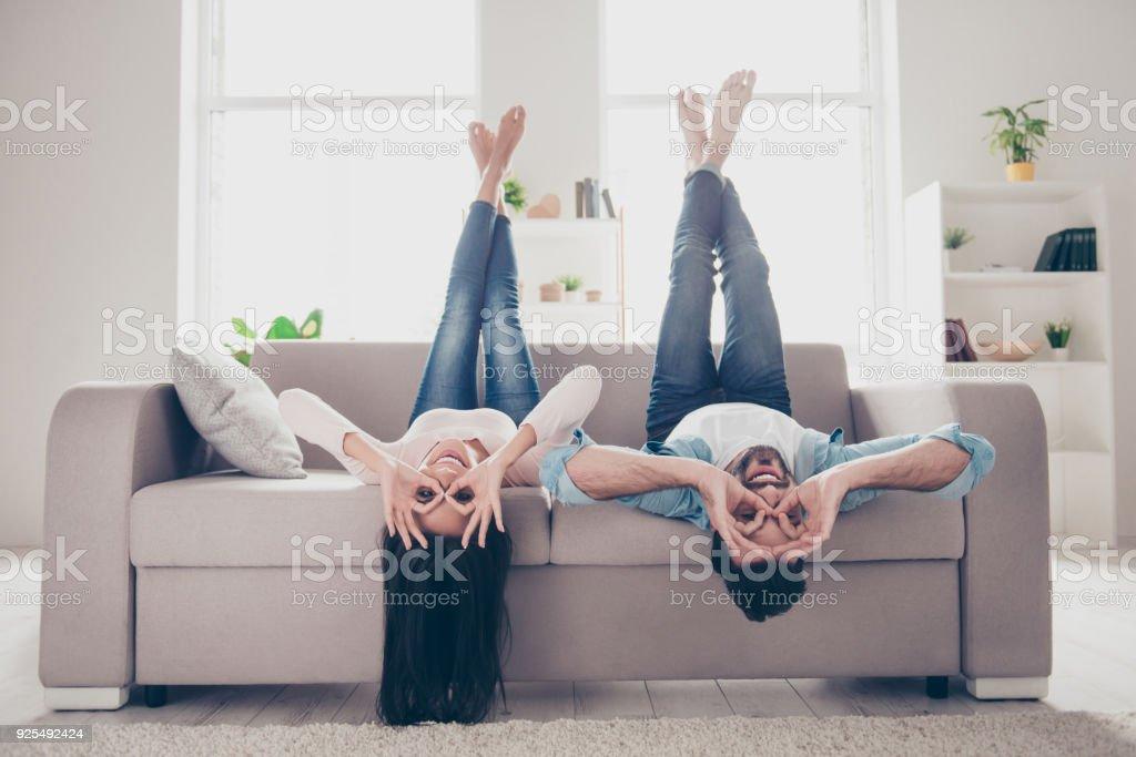 ¡Vamos loco y divertirse juntos! Hermosa pareja humorística encantadora alegre de dos amantes vestidos en denim casual outwear, demostrando prismáticos con las manos, tumbada boca abajo - foto de stock