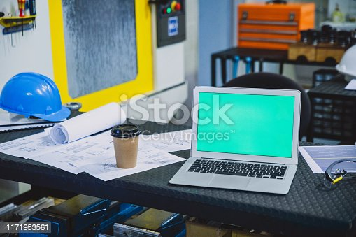 Shot of an empty engineering workshop with blueprints and a laptop on the table