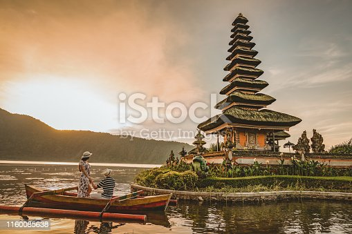 Happy romantic couple in love relaxing on honeymoon. The Ulun Danu Tamblingan Temple is located in the north side of Bali, in a Tamblingan lake. Tourist couple enjoying the lake. Photo of a couple on a boat in the lake at sunset looking at the temple.