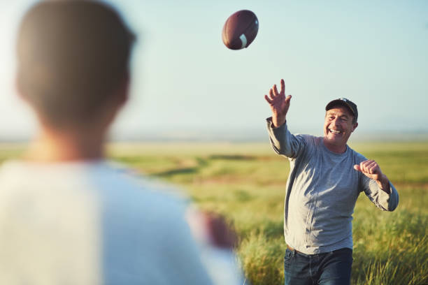 We have so much fun even when just tossing a ball Shot of father throwing a football to his son on a field american football ball stock pictures, royalty-free photos & images