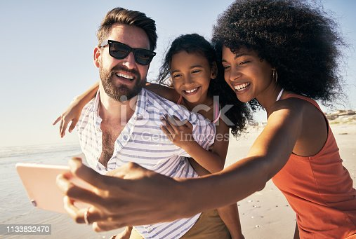 Shot of a happy family taking selfies together at the beach