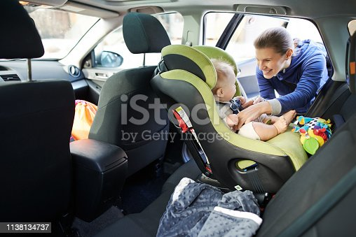 Portrait of a mother fastening her baby boy safely in a car seat