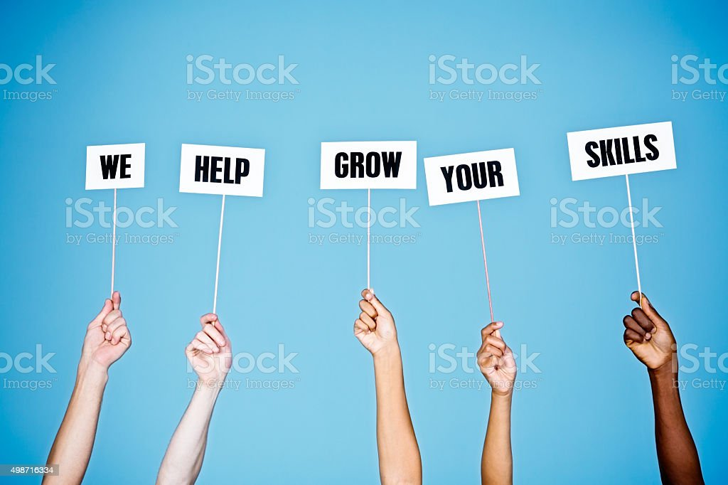 'We help grow your skills' say hand-held signs on blue stock photo