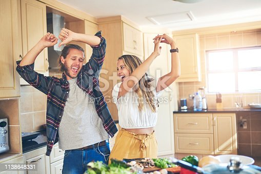 Shot of a couple listening to music while cooking in the kitchen