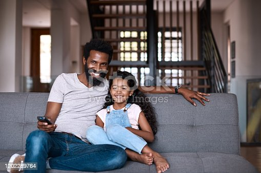 Shot of an adorable little girl watching tv and spending time with her father at home