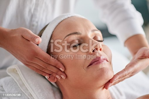 Shot of a mature woman getting a facial treatment at a spa