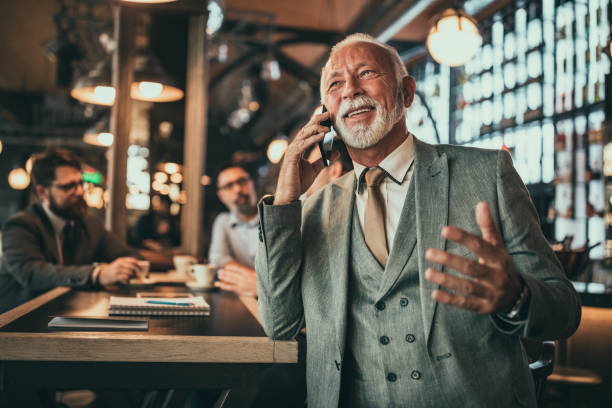 We live in a connected world Shot of a senior businessman talking on the phone in the pub old man working in a pub stock pictures, royalty-free photos & images
