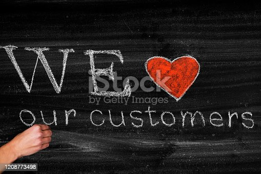 We love our customers,business concept on blackboard
