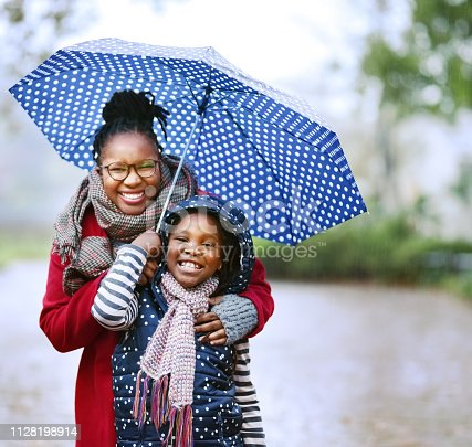 Shot of a mother and daughter under an umbrella outdoors in rain