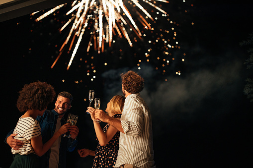 Four friends standing outside, toasting with glasses of wine and watching fireworks