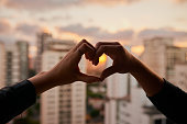 Cropped shot of an unrecognizable couple making a heart shape with their hands against a city background