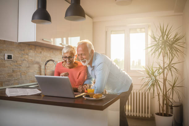 We love to video chat with our family Senior couple staying in touch with their family using their laptop at home 55 59 years stock pictures, royalty-free photos & images