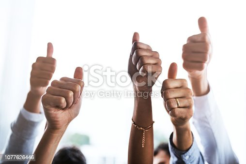 Closeup shot of a group of businesspeople showing thumbs up in an office