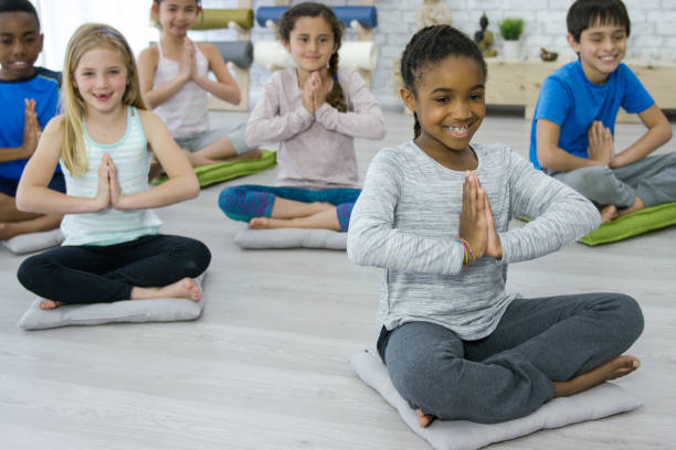 We Love Yoga Class Cute young elementary age girl of african descent wearing a grey shirt sitting on a cushion smiling and holding prayer pose with a multi-ethnic group of kids during a yoga class in a bright white studio. prayer pose yoga stock pictures, royalty-free photos & images