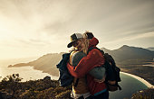 Cropped shot of an affectionate young couple embracing while hiking through the mountains