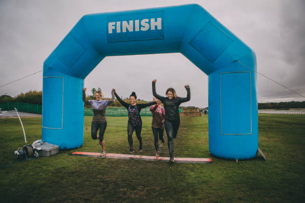 We Made It! Group of friends are running over the finish line at a charity obstacle course. They are holding hands and are covered in mud and water. obstacle course stock pictures, royalty-free photos & images