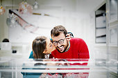 Attractive couple buying jewelry together in a jewelry store. They just made a choice for their engagement rings. Woman is hugging her man and kissing him on a cheek. They are smiling and they are happy.