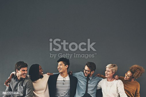 Studio shot of a diverse group of creative employees embracing each other against a grey background