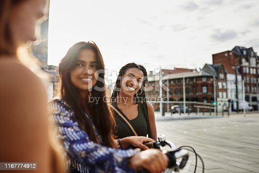 Cropped shot of three happy young friends walking through the city together while one pushes a bicycle