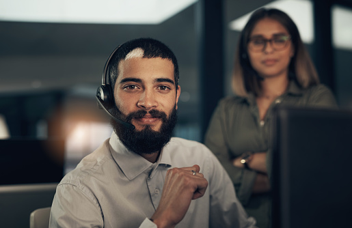 Portrait of a call centre agent working in an office alongside a colleague at night