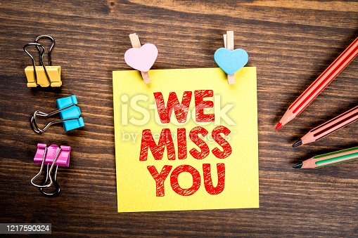 We Miss You. Reminder, Call, Relationships and Marketing concept. Wooden clips with heart and note on wooden table