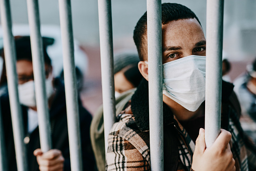 Shot of a young man wearing a mask while stuck behind a gate in a foreign city
