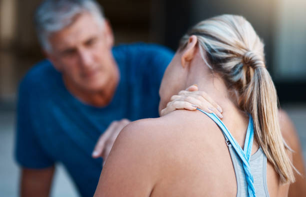 We need get that checked out asap honey Shot of a mature woman holding her neck in pain after an intense workout session with her husband ASAP stock pictures, royalty-free photos & images