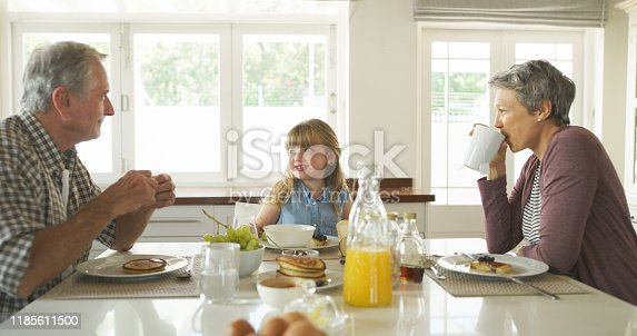 Shot of a little girl having breakfast with her grandparents at home