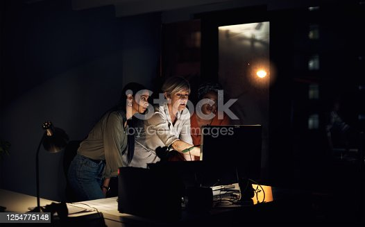 Shot of a group of businesswomen working together on a computer in an office at night