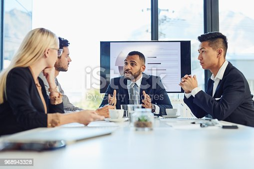 Shot of a group of young businesspeople having a meeting in the boardroom of a modern office